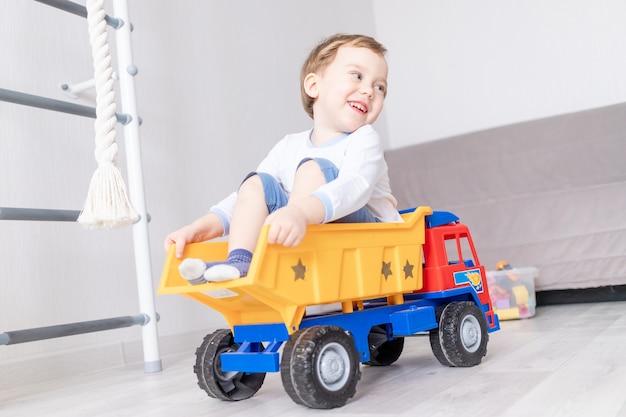 Gelukkig babyjongen spelen thuis, rijden in een typemachine, het concept van een kinderspel.
