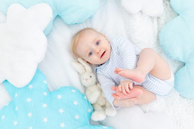 Gelukkig babyjongen zes maanden oud liggend op het bed met een knuffel konijn, schattige blonde baby