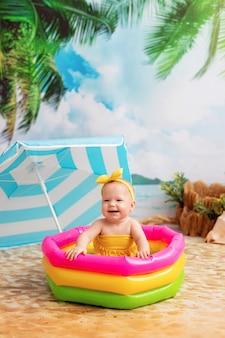 Gelukkig babymeisje baadt in heldere opblaasbaar zwembad op een zandstrand met palmbomen aan zee