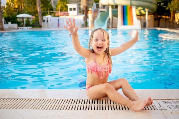 Gelukkig babymeisje bij het zwembad met waterglijbanen schreeuwt hoera en lacht plezier op vakantie, haar handen opstekend, het concept van recreatie en reizen