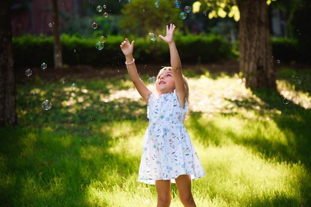 Gelukkig babymeisje dat zich in gras met paardebloemen bevindt