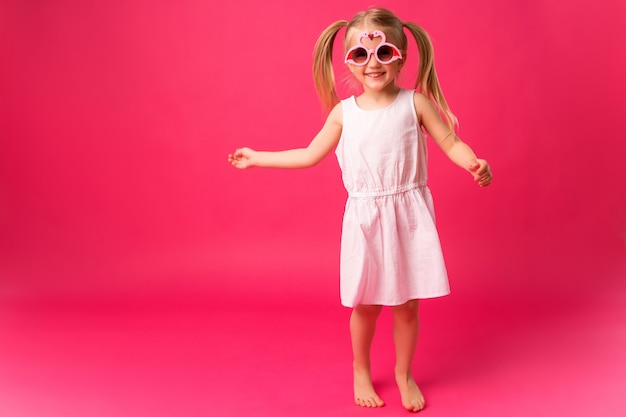Gelukkig babymeisje die in zonnebril op roze achtergrond glimlachen