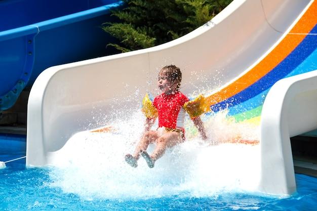 Gelukkig babymeisje glijdt vreugdevol van de waterglijbaan in het zwembad in de zomervakantie