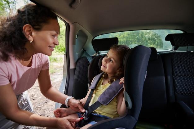 Gelukkig babymeisje glimlacht terwijl ze naar haar lachende moeder kijkt terwijl ze haar in de autogordel zet. veilig verplaatsen van kinderen in de auto