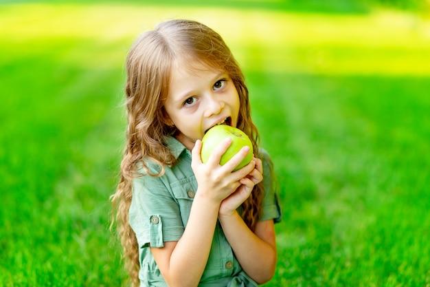 Gelukkig babymeisje in de zomer op het gazon bijt een groene appel met gezonde tanden op het gras en glimlacht, ruimte voor tekst