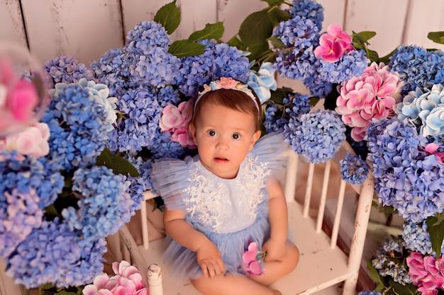 Gelukkig babymeisje in een jurk in de studio op een witte achtergrond met roze en blauwe hortensia bloemen