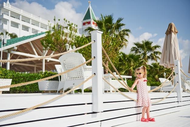 Gelukkig babymeisje in een jurk op het strand aan zee in de zomer.