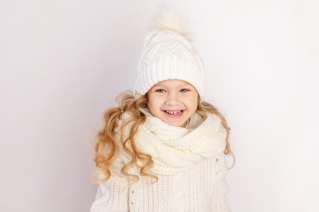 Gelukkig babymeisje in warme muts en trui op witte geïsoleerde achtergrond, ruimte voor tekst
