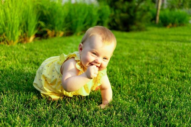 Gelukkig babymeisje kruipt en loopt op het groene gazon in de zomer in het park
