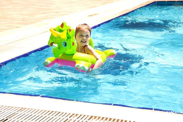 Gelukkig babymeisje leert lachend zwemmen in het zwembad in de zomer