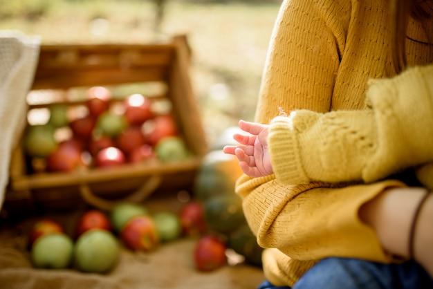 Gelukkig babymeisje met een mand met appels buiten in de herfst park
