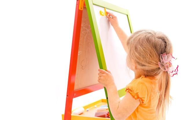 Gelukkig babymeisje mooi schilderij op de ezel op een witte achtergrond