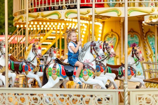 Gelukkig babymeisje rijdt een carrousel op een paard in een pretpark in de zomer