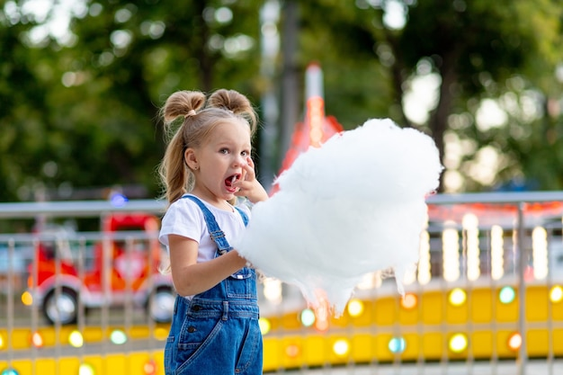 Gelukkig babymeisje suikerspin eten in pretpark in de zomer