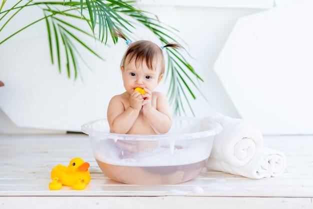 Gelukkig babymeisje wast in een bak met schuim en water in een lichte kamer thuis en speelt met een gele rubberen eend