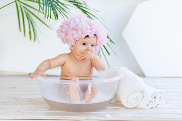 Gelukkig babymeisje wast in een bak met schuim en water in een lichte kamer thuis in een mooie badmuts gemaakt van bloemen