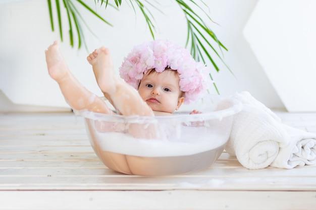 Gelukkig babymeisje wast in een bak met schuim en water