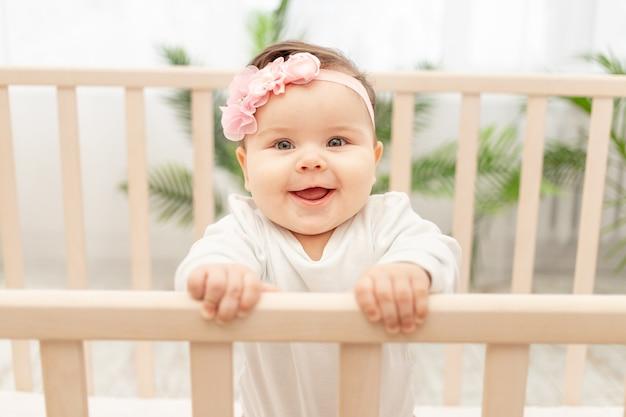Gelukkig babymeisje zes maanden permanent in de wieg