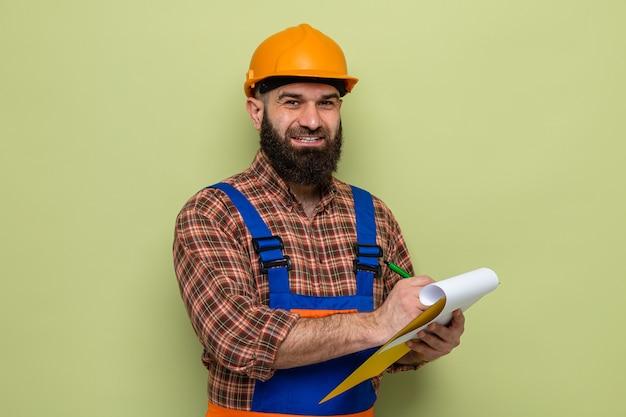 Gelukkig bebaarde bouwman in bouwuniform en veiligheidshelm met klembord met blanco pagina's die aantekeningen maken die vrolijk glimlachen