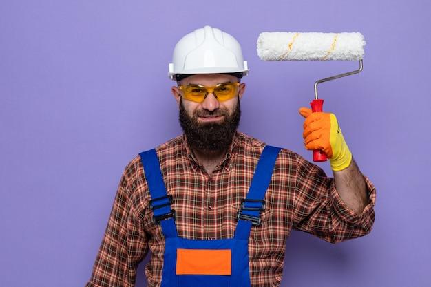 Gelukkig bebaarde bouwman in bouwuniform en veiligheidshelm met rubberen handschoenen die een verfroller vasthoudt en er vrolijk glimlachend uitziet smiling
