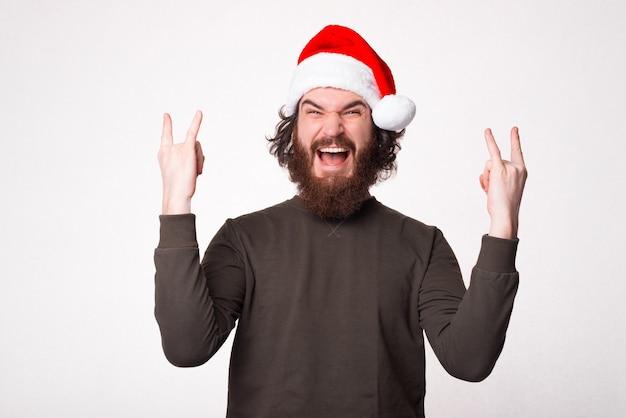 Gelukkig bebaarde hipster man rock gebaar tonen