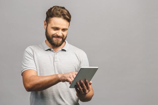 Gelukkig bebaarde jonge man in casual staande en met behulp van tablet