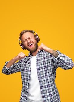 Gelukkig bebaarde man dansen en zingen samen met gesloten ogen tijdens het luisteren naar muziek in koptelefoon tegen geel