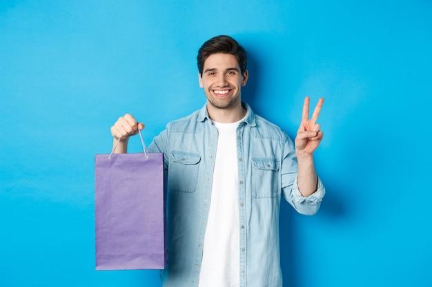 Gelukkig bebaarde man die papieren zak uit de winkel houdt en vredesteken toont, staande over de blauwe muur