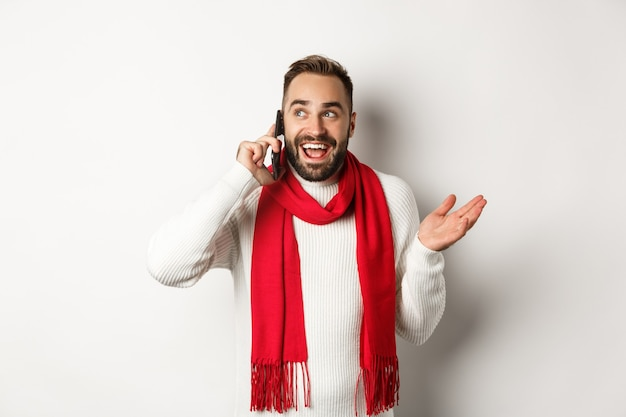Gelukkig bebaarde man die vrolijk kerstfeest wenst op de telefoon, iemand belt en praat, staande in een trui met rode sjaal, witte achtergrond.