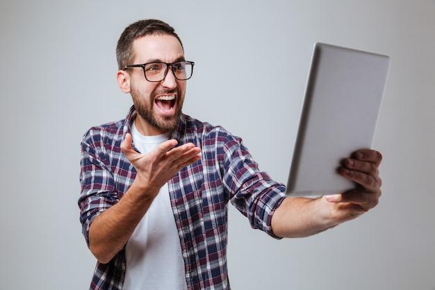 Gelukkig bebaarde man in bril maken selfie op tablet pc