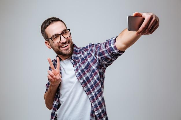 Gelukkig bebaarde man in bril maken selfie