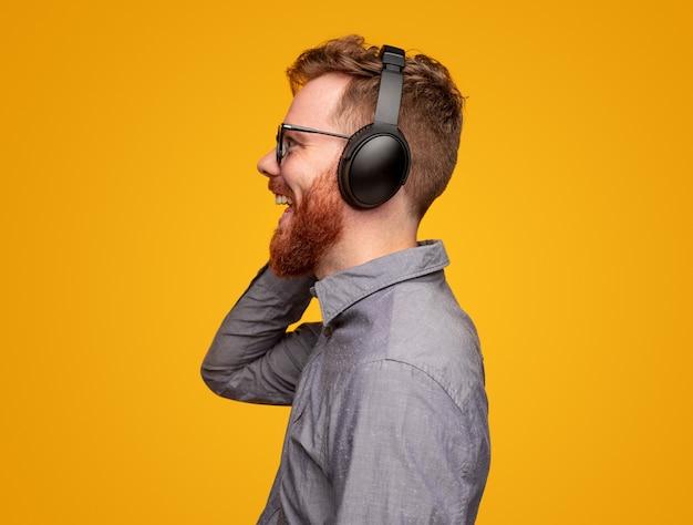 Gelukkig bebaarde man in koptelefoon genieten van muziek