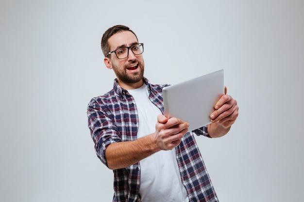 Gelukkig bebaarde man in oogglazen spelen op tablet pc