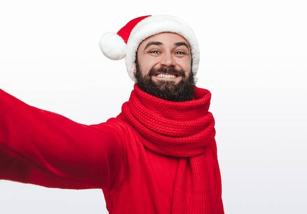 Gelukkig bebaarde man in rode sjaal en kerstmuts glimlachend en selfie te nemen