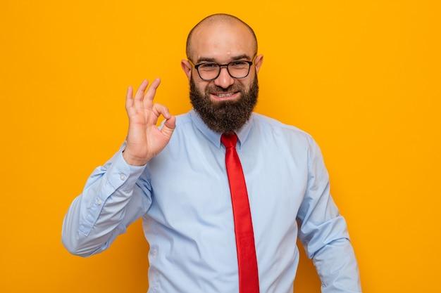 Gelukkig bebaarde man in rode stropdas en blauw shirt met een bril die kijkt met een glimlach die een goed teken toont Gratis Foto