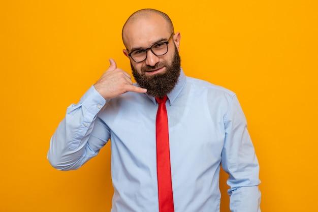 Gelukkig bebaarde man in rode stropdas en shirt met bril kijken naar camera glimlachend maken bel me gebaar staande over oranje achtergrond