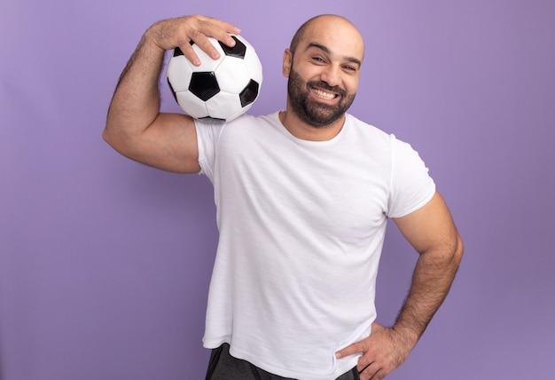Gelukkig bebaarde man in wit t-shirt met voetbal op zijn schouder glimlachend staande over paarse muur