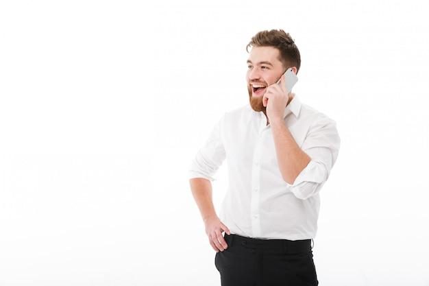 Gelukkig bebaarde man in zakelijke kleding praten door smartphone