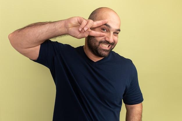 Gelukkig bebaarde man in zwart t-shirt glimlachend vrolijk tonen v-teken in de buurt van zijn oog staande over groene muur