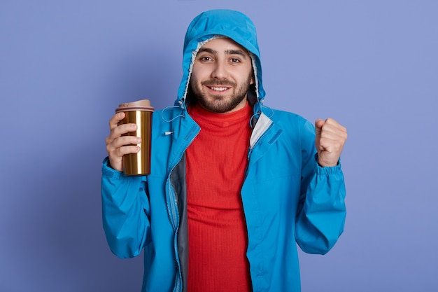 Gelukkig bebaarde man met blauwe jas en rood shirt genieten van warme drank uit thermomok en balde vuisten,
