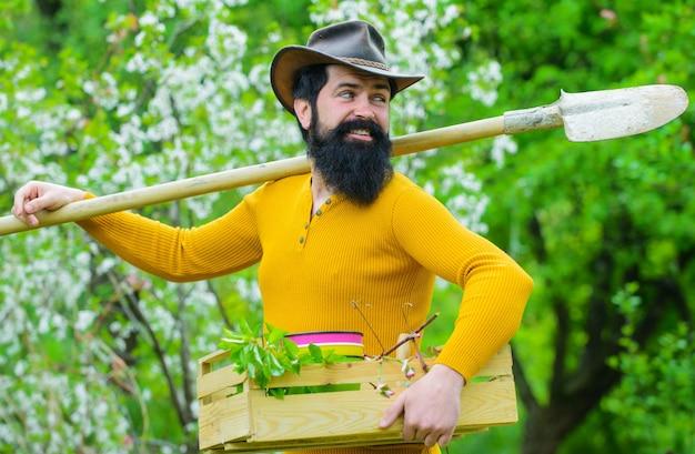 Gelukkig bebaarde man met tuingereedschap in de tuin.