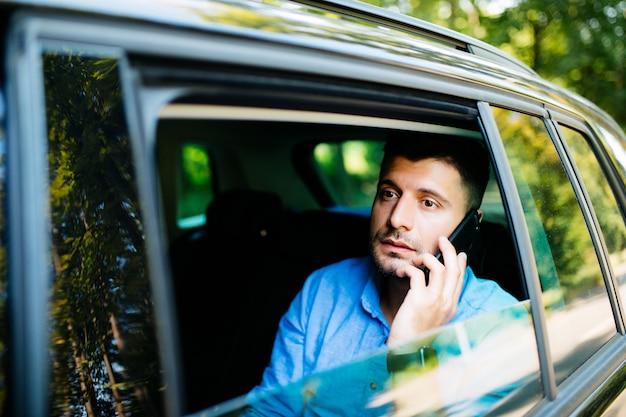 Gelukkig bebaarde man praten over mobiele telefoon zittend op de achterbank van de auto