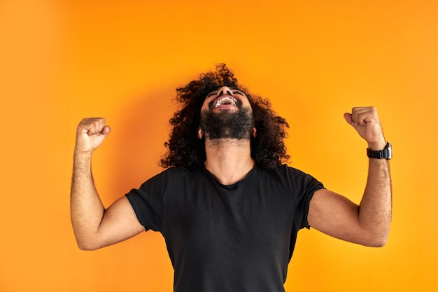 Gelukkig bebaarde man viert zijn winnende, glimlach, krullende man schittert van geluk