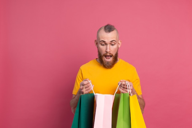 Gelukkig bebaarde positieve man casual look met kleurrijke boodschappentassen studio roze achtergrond