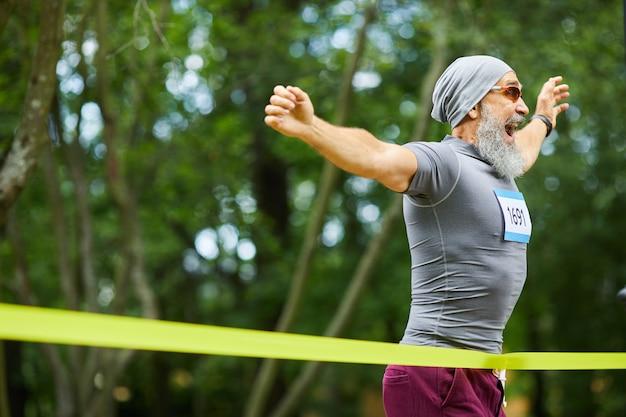 Gelukkig bebaarde senior man met pet en zonnebril winnen van de eerste plaats in de marathonrace, kopie ruimte