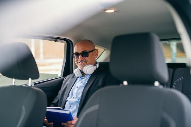 Gelukkig bebaarde senior volwassen zakenman zittend op de achterbank van de auto met koptelefoon rond de nek en agenda in handen.