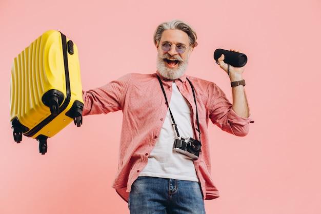 Gelukkig bebaarde stijlvolle man in zonnebril met camera met een koffer en een draagbare luidspreker