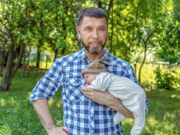 Gelukkig bebaarde vader met pasgeboren baby op zijn armen in het park op zonnige zomerdag