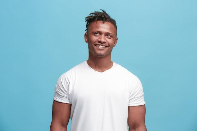 Gelukkig bedrijfsmens permanent en glimlachend geïsoleerd op blauwe studioachtergrond. african american mannelijke halve lengte portret. jonge emotionele man. de menselijke emoties, gezichtsuitdrukking concept. vooraanzicht.