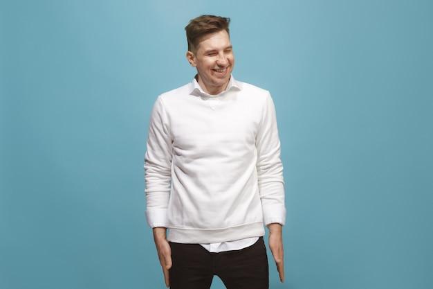 Gelukkig bedrijfsmens permanent en glimlachend geïsoleerd op blauwe studioachtergrond. mooi mannelijk portret van halve lengte. jonge emotionele man. de menselijke emoties, gezichtsuitdrukking concept. vooraanzicht.